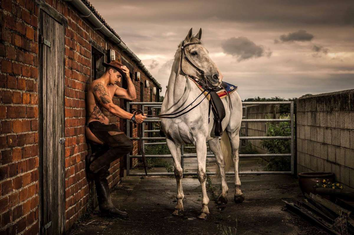 Photo of man dressed as a cow boy holding a beautiful grey horse in tack. Taken for the Hunks and Horses charity calendar for testicular cancer research UK and World Horse Welfare.