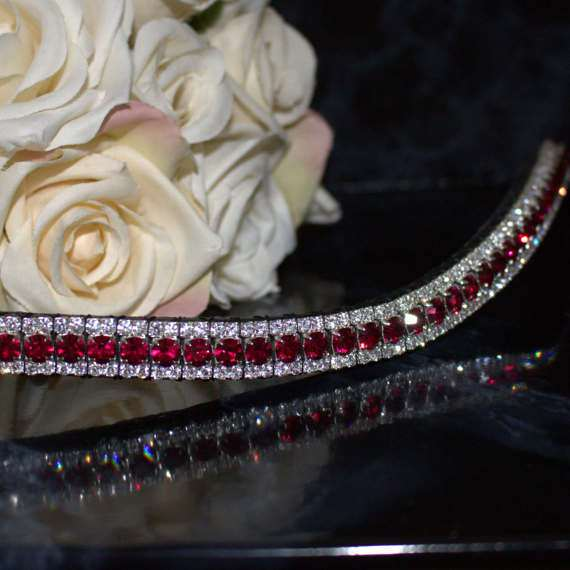 Ruby and Clear Triple Crown Range of Crystal Bling browbands and with Red crystals on a red browband with a black back ground and white flowers for a dressage horse