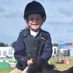 Maisie Farnham riding her pony at a showjumping competition.