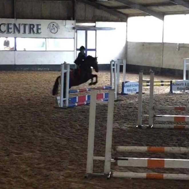 Maisie Farnham riding her pony Magic in an indoor arena at Moorhouse Equestrian Center showjumping and on a black pony at Moorhouse EC