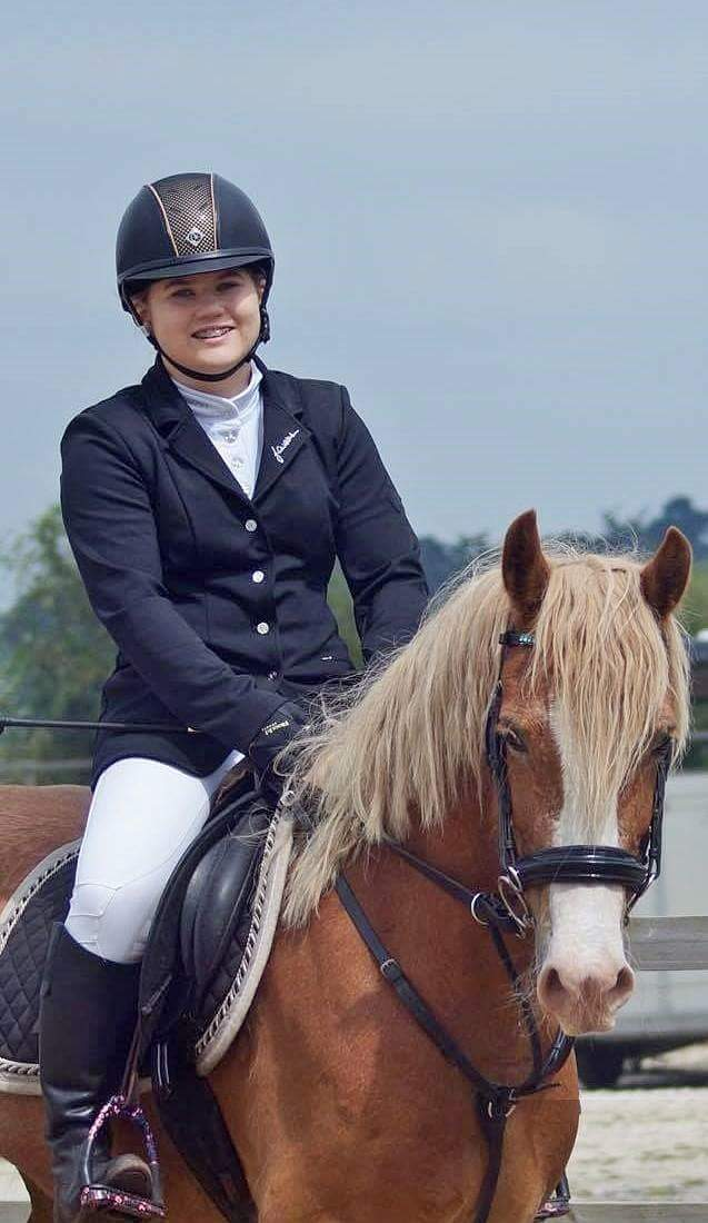 Ruth walker riding her chestnut horse at a competition wearing a navy show jacket and riding hat in a saddle.